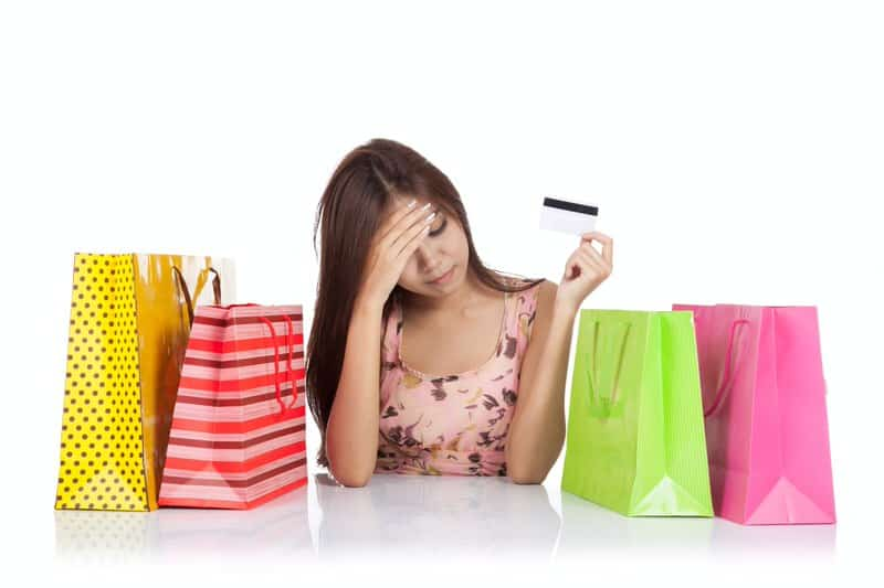 Worried Woman With Credit Card and Shopping Bags