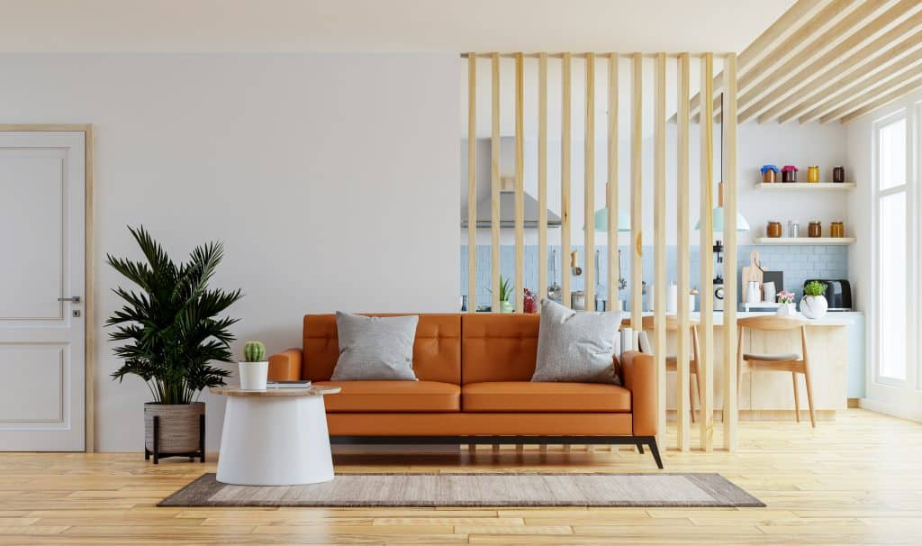 Living room interior wall mockup in warm tones with leather sofa which is behind the kitchen.3d rendering